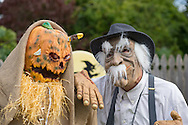 Merrick, New York, USA. October 29, 2016. At right, JIM JOHNSON, of Merrick, wearing a Munchkin costume from Wizard of Oz, is standing outside his front yard decorated in a scary spooky Wizard of Oz theme, to entertain people as they walk across the street to the entrance of Fraser Park for the 2016 annual Merrick Spooktacular hosted in part by the North and Central Merrick Civic Association (NCMCA). JOHNSON's hand rested on a ghoulish, gruesome Straw Man lawn decoration, with a daggner plunged into its pumpkin head.