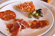 In the restaurant. Tomato on bread. Dry cured ham. Sausages. Charcuteries.  Herdade da Malhadinha Nova, Alentejo, Portugal