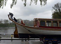 © Licensed to London News Pictures. 19/04/2012. London, UK .A man climbs onto the stern to prepare the barge. The Royal barge Gloriana is  lowered into the River Thames today for the first time. Gloriana was designed to resemble vessels in Canaletto's famous painting of an 18th century river pageant on the Thames Gloriana will be rowed by eighteen oarsmen, including Britain's Olympian Sir Steven Redgrave. It will lead a pageant of more than 1,000 boats will sail down the Thames on June 3 to mark the 60th anniversary of Her Majesty's reign . Photo credit : Stephen Simpson/LNP