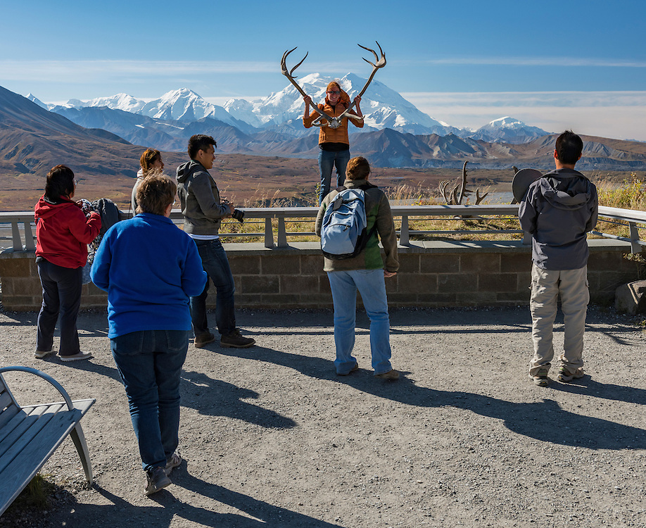 A group of people with one woman holding caribou antlers at her side at Eielson Visitor Center with Denali (formerly Mt. McKinley) looming in the background on a clear fall day. Denali National Park, Alaska PLEASE CONTACT US FOR DIGITAL DOWNLOAD AND PRICING.