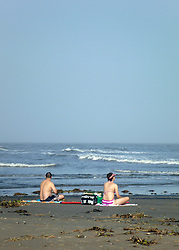 26 December 2015. Grand Isle, Louisiana.<br /> Boxing Day on the beach. A couple enjoy unseasonably warm temperatures boogie boarding at the beach.<br /> Photo©; Charlie Varley/varleypix.com