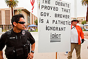 22 OCTOBER 2010 - PHOENIX, AZ:  An Arizona Capitol police officer watches BILL DEMSKI, from Glendale, AZ, and an opponent of the Tea Party, after Demski was asked to leave a Tea Party rally in Phoenix. About 300 people attended a Tea Party rally on the lawn of the Arizona State Capitol in Phoenix Friday. They demanded lower taxes, less government spending, repeal of the health care reform bill, and strengthening of the US side of the US - Mexican border. They listened to Arizona politicians and applauded wildly when former Alaska Governor Sarah Palin and her son, Trig, made a surprise appearance. The event was a part of the Tea Party Express bus tour that is crossing the United States.     Photo by Jack Kurtz