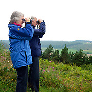 A pair of birdwatchers holding binoculars, North York Moors National Park, North Yorkshire, UK