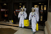 London 8/1/13: Two characters dressed as NASA moon walking astronauts, emerge outside on Oxford Street outside the Selfridges department store in central London. Emerging from the front doors of this famous shop, the two spacemen carry the famous yellow bags as other shoppers go in and out of the large doors. Selfridges, also known as Selfridges & Co, is a chain of high end department stores in the United Kingdom. It was founded by Harry Gordon Selfridge. The flagship store in London's Oxford Street is the second largest shop in the UK (after Harrods) and opened 15 March 1909