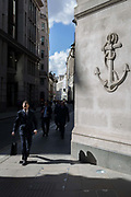 Passers-by beneath a carved anchor on a street corner in the Square Mile, the capitals financial district, on 31st March 2017, in the City of London, England.
