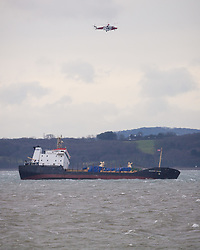 © Licensed to London News Pictures. 27/12/2017. Lee-on-Solent, UK.  The Coastguard helicopter flies overhead as the stricken Russian cargo vessel, Mekhanic Yartsev, braces the strong winds this morning. The Maritime and Coastguard Agency are formulating a plan to move her to Southampton. 13 crew members were rescued yesterday when the vessel developed a list, so made her way into the sheltered waters of The Solent before the weather conditions deteriorated. Photo credit: Rob Arnold/LNP