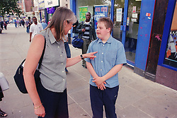 Mother standing in street telling off teenage son with Downs Syndrome,