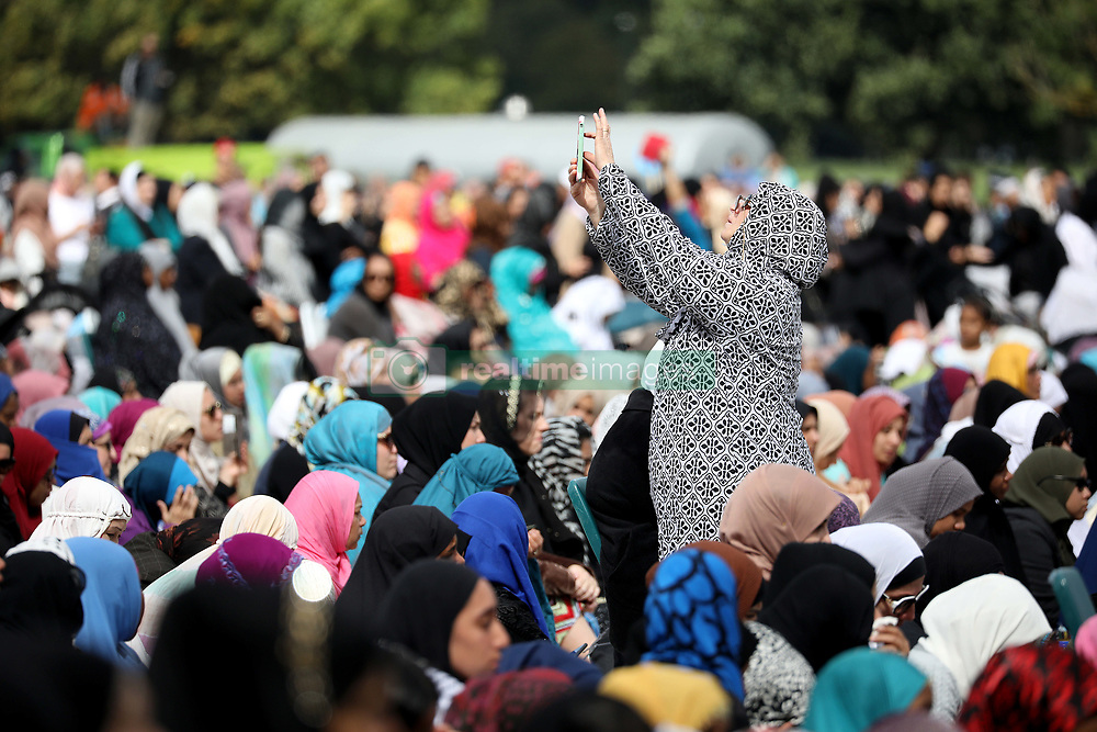 March 23, 2019 - Christchurch, New Zealand - A Muslim woman takes pictures with a smartphone during Friday Islamic prayers in Hagley Park outside the Masjid Al Noor mosque in Christchurch, New Zealand on March 22, 2019. Vigils took place around the country to pay respect to the victims of Christchurch's terror attack, a week after the horrific shooting killed 50 people in two mosques. A 28-year-old Australian born man, Brenton Tarrant has been charged with murder following the attacks. (Credit Image: © Sanka Vidanagama/NurPhoto via ZUMA Press)