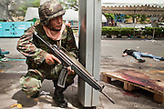 May 19 - BANGKOK, THAILAND: A Thai soldier takes shelter in a bus stop in Lumpini Park while a dead anti government protester lies in the street during the Thai government crack down against Red Shirt and anti government protesters. The Royal Thai Army attacked anti-government protesters May 19 with troops and armored personnel carriers. More than 90 people were killed during the crackdown.  Photo by Jack Kurtz