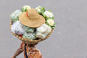 Woman with basket of cauliflower o her head with hat on top, Zay Cho Market, Mandalay