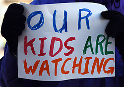 """December 10, 2016 - Washington, DC, USA - A man holds a sign saying ''Our Kids Are Watching''.  Children's Rally for Kindness takes place at Trump International Hotel in Washington DC on December 10, 2016 organized by the Takoma Parents Action Coalition.  According to their FaceBook page, it was a call to President-elect Donald Trump: ''to remember these lessons as he prepares to take office and implement policies that will affect the lives of children and families across our diverse nation.''.''All over the world, across cultures and countries, children learn the same basic lessons: .Ã'be kind,Ã"""" .Ã'tell the truth,Ã"""" .Ã'be fair,Ã"""" .Ã'respect everyone,Ã"""" .Ã'treat others the way you want to be treated,Ã"""" .Ã'donÃ•t touch others if they donÃ•t want to be touched. (Credit Image: © Carol Guzy via ZUMA Wire)"""