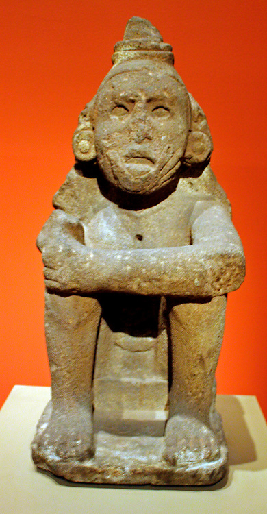 Aztec Standard Bearer. Seated on a small plinth with arms on knees and legs drawn up towards the body, this male figure wears an important headdress that was once topped with five tall tufts.  The tufts, related to the crest of a great curassow, are now missing, but in the back, the head covering still hangs onto the shoulders, where the figure's name, 5 Serpent, is carved.