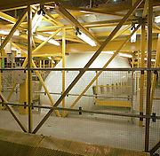 During a lull in activity, a Boeing 747 is swathed in engineering gantries during a major check (maintenance schedule) at the British Airways Heathrow base in London England. As if in a hospital ER several metres off the ground, yellow struts surround the aircraft's forward nose section and the first class windows along the white fuselage allowing mechanics, engineers and avionics specialists unimpeded access to every element of the air frame. Neon tubes illuminate the hangar that houses flying machines which are serviced here between transcontinental commercial passenger flights. Picture from the 'Plane Pictures' project, a celebration of aviation aesthetics and flying culture, 100 years after the Wright brothers first 12 seconds/120 feet powered flight at Kitty Hawk,1903. .