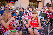30 JUNE 2012 - PRESCOTT, AZ:   Children watch the the Prescott Frontier Days Rodeo Parade. The parade is marking its 125th year. It is one of the largest 4th of July Parades in Arizona. Prescott, about 100 miles north of Phoenix, was the first territorial capital of Arizona.   PHOTO BY JACK KURTZ