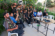 A group of armed men of the Free Syrian Army are seen taking a break following a military operation in the region of Azaz on Sunday, June 10, 2012. (Photo by Vudi Xhymshiti)