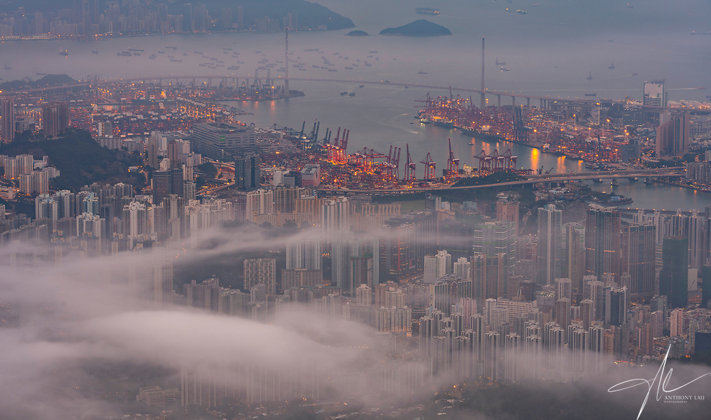 Early in the morning, low altitude clouds emerged and about to cover the whole Hong Kong city.  I captured this contrasting shot where the now-quiet residential and commercial districts blanketed under the cloud, leaving the 24-hours operational cargo terminal open to clear sky.