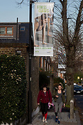 Two young women walk towards the new GLL Greenwich Leisure Limited gym passing beneath banners opposite Carnegie Library on Herne Hill SE24, on 10th February 2019, in London, England.