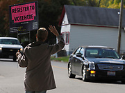 Voting registration volunteer Debra Dunlop waves to drivers to encourage those who have yet to register to do so at the nearby voter registration site.