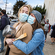 """Hayley Rowley, 27, in knit cap and girlfriend Sarah Mann, 28, join a celebration on a corner in Studio City, CA after the announcement on November 7, 2020 that Joe Biden would be the 46th President of the United States. """"I feel like I can breathe again,"""" Hayley said after getting emotional."""