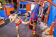 """18 DECEMBER 2104 - BANGKOK, THAILAND: A boxer works out by kicking the heavy bag at the Kanisorn gym. The Kanisorn boxing gym is a small gym along the Wong Wian Yai - Samut Sakhon train tracks. Young people from the nearby communities come to the gym to learn Thai boxing. Muay Thai (Muai Thai) is a Thai fighting sport that uses stand-up striking along with various clinching techniques. It is sometimes known as """"the art of eight limbs"""" because it is characterized by the combined use of fists, elbows, knees, shins, being associated with a good physical preparation that makes a full-contact fighter very efficient. Muay Thai became widespread internationally in the twentieth century, when practitioners defeated notable practitioners of other martial arts. A professional league is governed by the World Muay Thai Council. Muay Thai is frequently seen as a way out of poverty for young Thais and Muay Thai camps and schools are frequently crowded. Muay Thai professionals and champions are often celebrities in Thailand.     PHOTO BY JACK KURTZ"""