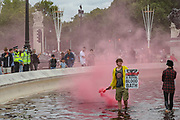 """An Animal and climate activist from the Animal Rebellion activists group holds a red flare as they walk in the red-colour dyed fountain outside Buckingham Palace on Thursday, Aug 26, 2021 - signifying as their statement said """"its' demonstrable role in hunting and animal agriculture"""". (VX Photo/ Vudi Xhymshiti)"""
