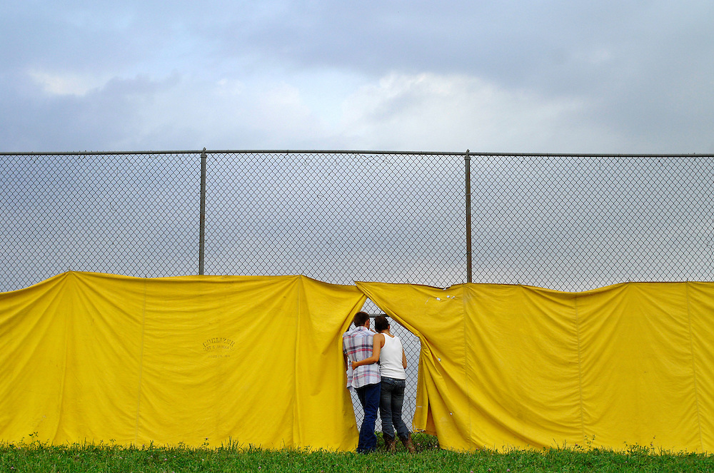 Johnny Izgrig, 17, and Leslie Rice, 16, of Centralia, cuddle as they watch the side-by-side mud racing through the Grandstand fence.