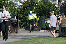 © Licensed to London News Pictures. 10/04/2020. London, UK. Police leave Primrose Hill in London after cycling past people sunbathing, during a pandemic outbreak of the Coronavirus COVID-19 disease. The public have been told they can only leave their homes when absolutely essential, in an attempt to fight the spread of coronavirus COVID-19 disease. Photo credit: Ben Cawthra/LNP