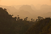 Mountain top view from Tiger Temple, Krabi, Thailand. Dramatic limestone karst formations form layers in the hazy sunset