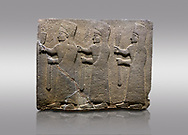 Picture & image of Hittite monumental relief sculpted orthostat stone panel of a Procession. Basalt, Karkamıs, (Kargamıs), Carchemish (Karkemish), 900-700 B.C.  Marching female figures. Anatolian Civilisations Museum, Ankara, Turkey.<br /> <br /> It is a depiction of three marching female figures in long dress with a high headdress at their head. These women are considered to be the nuns of the Goddess Kubaba. They have a bunch of Spica in their right hand, and objects similar to a sceptre in their left hand.<br /> <br /> Against a gray background. .<br />  <br /> If you prefer to buy from our ALAMY STOCK LIBRARY page at https://www.alamy.com/portfolio/paul-williams-funkystock/hittite-art-antiquities.html  - Type  Karkamıs in LOWER SEARCH WITHIN GALLERY box. Refine search by adding background colour, place, museum etc.<br /> <br /> Visit our HITTITE PHOTO COLLECTIONS for more photos to download or buy as wall art prints https://funkystock.photoshelter.com/gallery-collection/The-Hittites-Art-Artefacts-Antiquities-Historic-Sites-Pictures-Images-of/C0000NUBSMhSc3Oo