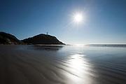 Sunburst over beach near lighthouse on Ilha do Mel, Brazil