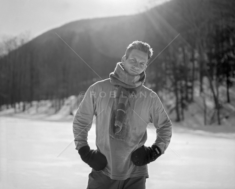 man with a large scarf and gloves outdoors in the Wintertime with flare from the sun behind his head