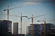 Four cranes and three buildings under construction on a building site in West Hanoi, Vietnam, Asia.