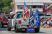 A pickup truck with various flags and Trump/Pence sign is seen in the Independence Day Parade in Millville, Pennsylvania on July 5, 2021.