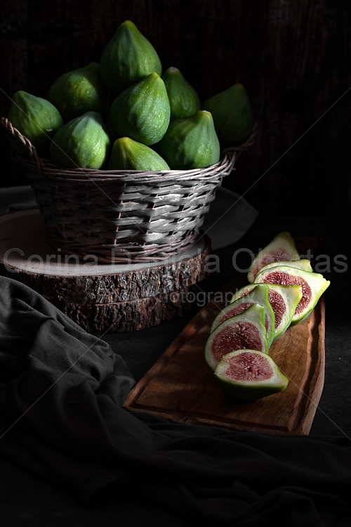Still life with figs inside a basket on old wooden table.