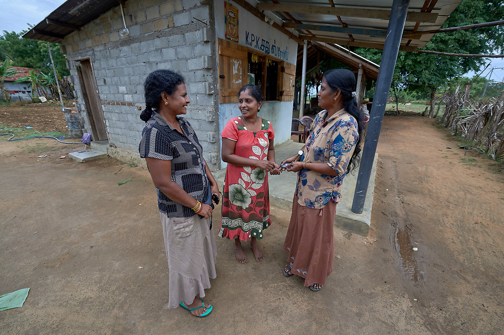Pramila Kirubajhas (center) is proud owner of a small shop in Karadianaru, Sri Lanka. Once displaced by Sri Lanka's bloody civil war, when she moved back home after the fighting ended, a church group loaned her money to open the store. Her profits have enabled her to pay for her children's education and improve the family diet. <br /> <br /> With her are Sasikala Thavarasa (left) and Krishnaveni Puthisikamani. All three are members of a local women's empowerment group sponsored by the Church of the American Ceylon Mission, which provided the funding for her store.