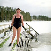 A portrait of a woman after ice swimming at Luonetjarvi lake, Tikkakoski; Central Finland. Ice swimming takes place in a body of water with a frozen crust of ice, which requires a hole cutting in it.  In Finland, the ice swimming tradition has generally been connected with the sauna tradition and it is not seen as an ascetic or religious ritual, but as a way to cool off rapidly after staying in the sauna and as a stress relief.