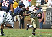 Oct 2, 2010; Charlottesville, VA, USA; Florida State Seminoles cornerback Greg Reid (5) is tackled by Virginia Cavaliers safety Trey Womack (1) during the game at Scott Stadium. Florida State won 34-14.  Mandatory Credit: Andrew Shurtleff-