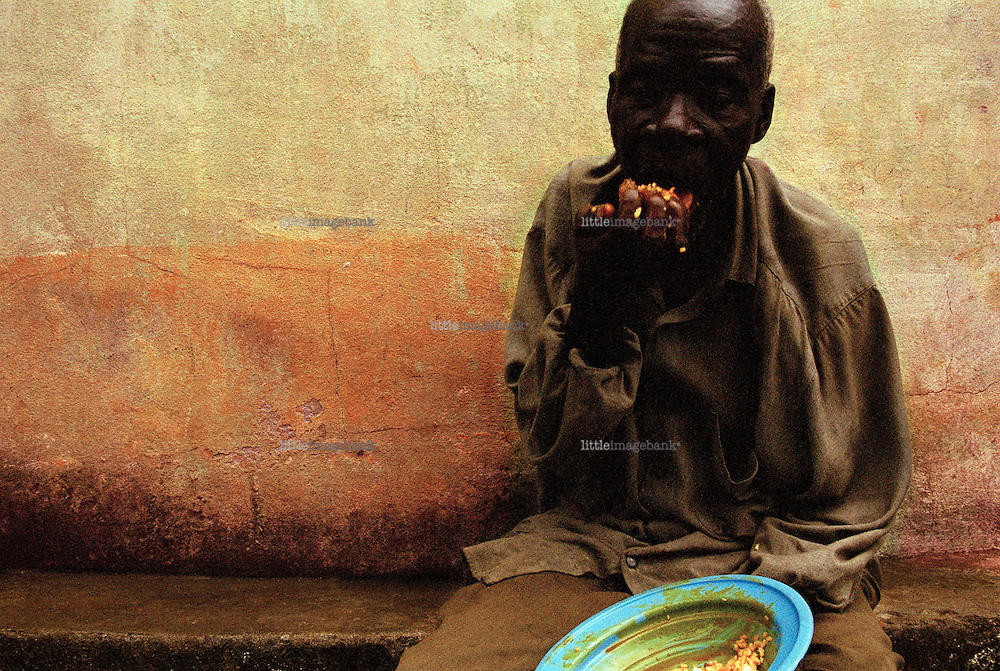 A man sits in a closed courtyard eating his daily meal. According to the United Nations Development Programme (UNDP), Sierra Leone is one of the poorest nations on the face of earth. Recently it saw the end of a decade of civil-war, that caused an extreme suffering for the population. Tens of thousands became victims of armed forces on amphetamine, that cut limbs for fun, child soldiers armed to the teeth with Kalashnikows.  An entire population was driven away from their homes and the infrastructure was completely destroyed. Today thanks to some 15.000 soldiers from the UN-AMSIL peacekeeping force, order is restored and dailylife is again more or less as it once was. Many of those who saw the horrors of the war can manage to move on with their lives, many cant manage. <br /> Kissy Mental Hospital is located on a small hilltop on the north part of the capitol Freetown in a small suburbia named Kissy, The hospital compound was constructed in the mid 1800s under the bristish colonny empire. It has served several different purposes in the past, today it serves as the only institution for individuals suffering from mental illness in the whole country. <br /> The chief nurse tells that few turns back to narmality, some of the young boys are examples of success. He admits that its not the easiest place to become sane, rather a place that makes you insane.
