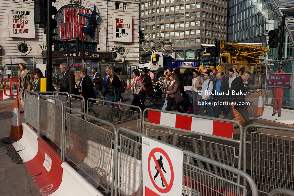 Londoners walk across a road crossing with temporary barriers and fencing during improvements in Victoria.