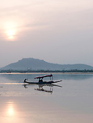 A shikara, a local wooden boat, at sunset on Lake Dal in Kashmir, India