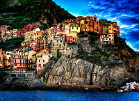 """""""Sunset view of Manarola from the blue Tyrrhenian Sea""""…<br /> <br /> I began my daily journey at the northernmost town of Monterosso and took the train to the southernmost town of Riomaggiore. I sailed up the coast photographing each Cinque Terre town along the way aboard the Angelina Dada.  This image was composed standing on the rooftop of the antique 28 foot Angelina's galley with my arms around the mast and my 25-pound camera bag strapped over my shoulder, creating a human tripod for support. I could not help noticing tourists in each village photographing our boat as we sailed up and down the coast; perhaps it was the image of a silly photographer hanging on for dear life as the waves wobbled the boat side to side in anticipation of a splashdown?! Leaving for my destination of Monterosso, the radiant sunset illuminated the sky and azure sea of the Mediterranean. I was convinced to sail back to Riomaggiore with my gracious guides Claudio and Eddie of """"Cinque Terre dal Mare"""" sailing excursions. We arrived just in time for the perfect magic-hour glow of the setting sun. After a nice dinner...I caught the last train at midnight back home to Monterosso.  I believe there is a great appeal in each of the five Cinque Terre villages, each with a different history, people, elements, and culture.  This illuminating sunset of Manarola was captured just before arriving back in Riomaggiore. Arrivederci, Manarola!"""