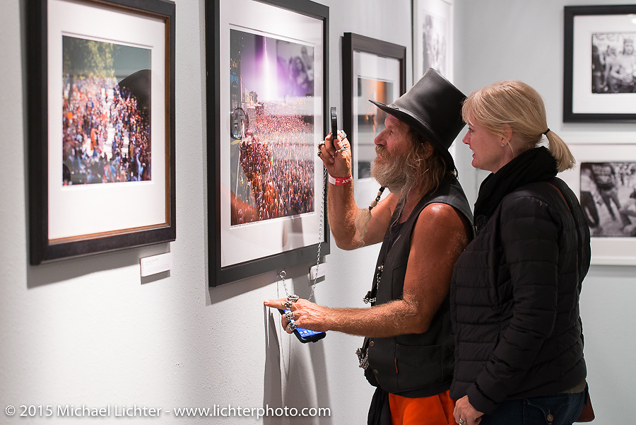 """Checking out the details in """"Lightning Strikes"""" print of a Kid Rock concert by Michael Lichter in his Motorcycles as Art annual exhibition titled """"The Naked Truth"""" at the Buffalo Chip Gallery during the 75th Annual Sturgis Black Hills Motorcycle Rally.  SD, USA.  August 4, 2015.  Photography ©2015 Michael Lichter."""