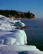 Winter ice along the shore of Lake Superior with Split Rock Lighthouse beyond on 130-foot high cliff, Split Rock Lighthouse State Park, Minnesota.