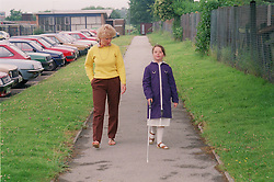 Teacher supervising young girl with visual impairment walking along path learning how to use white stick,