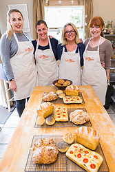 Jess Hayden, left, Susie Mullen and Hazel Griffiths with Baker Liz Wilson, 2nd right, who leads classes where participants learn a number of baking methods at her Fulham home in London. London, August 16 2019.