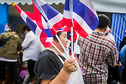17 FEBRUARY 2014 - BANGKOK, THAILAND: A woman sells Thai flags during protests in front of Government House. The anti-government protest movement, led by the People's Democratic Reform Committee and called Shutdown Bangkok has been going on for more than a month. The protest movement called, the People's Democratic Reform Committee (PDRC), wants to purge the current ruling party and its patrons in the Shinawatra family from Thai politics. The movement has consistently refused any dialogue or negotiations with the Pheu Thai ruling party. Over the weekend Thai police claimed to have taken the protest areas around Government House (the Prime Minister's office) away from protestors but on Monday protestors marched unimpeded to Government House and retook the area.   PHOTO BY JACK KURTZ