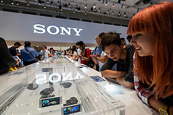 Visitors to Sony stand examine waterproof Xperia tablets and smart phones in water tank at IFA 2014 consumer electrical show in Berlin