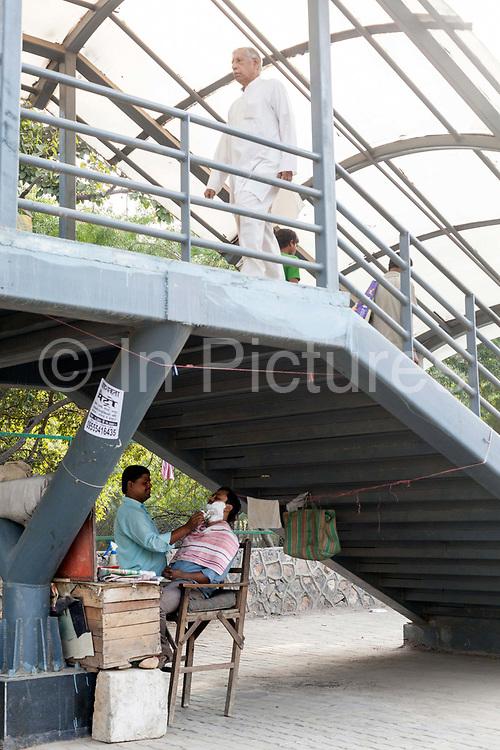 A barber shaves a customer beneath a pedestrian bridge across a main road, Vasant Vihar, New Delhi, India