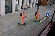 Wearing compulsory high-visibility industrial clothing, two construction workmen ride their eScooters across the pavement and wait to cross the road in Waterloo, on 22 February 2021, in London, England.