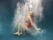 A model in red dress is diving in a pool surrounded by the cloud of bubbles.